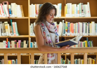 Female student reading a book against bookshelf in the library