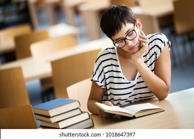 Female student reading a book at library