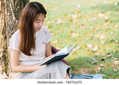 Female student reading a book under a tree after school.