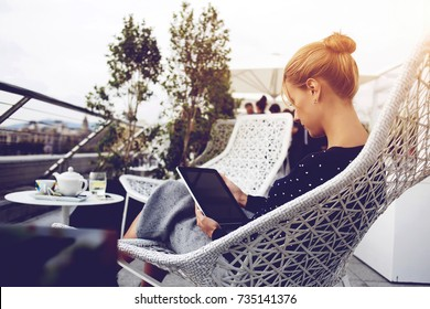 Female student is resting in cafe terrace and reading electronic book on touch pad during her free time before lectures. Woman successful employer is watching worlds news in network via digital tablet