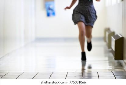 A female student runs through a corridor in a college