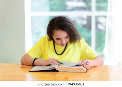 A female student sits at her desk and reads a large book in the classroom. Education for adults concept.