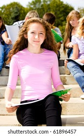 Female student sitting with book in hands, her friends behind