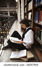 Female student sitting at bookshelf in old library reading books.
