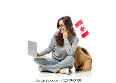 female student sitting with canadian flag and using laptop isolated on white