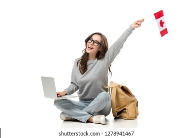female student sitting with laptop and cheering with canadian flag isolated on white