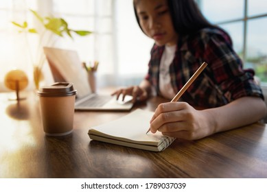 Female student sitting notes in diary and using laptop for homework during covid 19 pandemic and lockdown, Social Distance, New life of Student on internet. Online E-learning system in training course