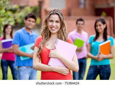 Female student smiling with a group behind ? outdoors