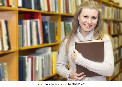 female student standing at bookshelf in old library searching for a book.