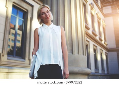 Female student standing near University building while posing with laptop computer for magazine alumni, young woman entrepreneur standing near architectural monument after planing work on net-book