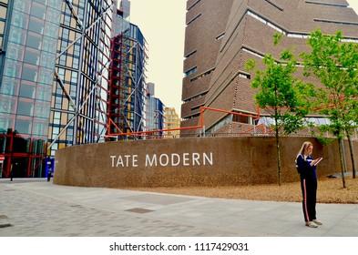 Female student standing outside the Tate Modern Art Gallery reading a street map. London Bankside, England UK. jUNE 2018
