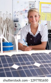 Female student studying wind solar power sources at school smiling at camera