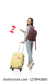 female student with suitcase and canadian flag looking at camera isolated on white, studying abroad concept