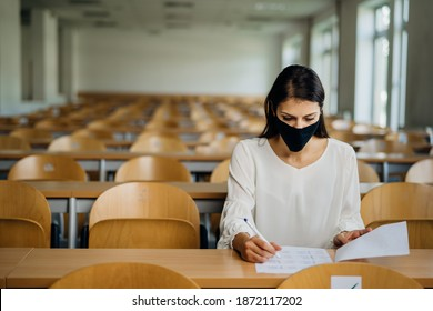 Female student taking an exam wearing a protective face mask in an empty amphitheater. Stressed student during COVID-19 outbreak.Coronavirus in-class test. Concerned woman having education evaluation