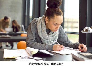 Female student taking notes from books for her study. Young african american woman sitting at table with books for finding information.