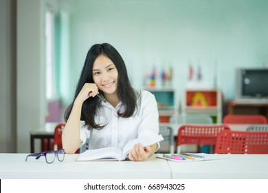 Female student taking notes preparing exam and learning lessons from a book at library. Young asian woman sitting at table doing assignments making research look at camera ,smiling in college librarys