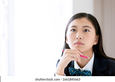 A female student thinking while studying