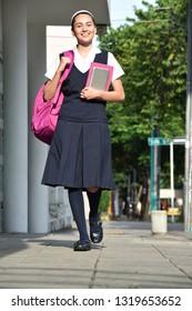 Female Student Walking On Sidewalk