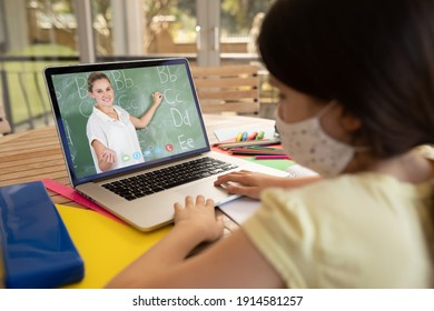 Female student wearing face mask having a video call with female teacher on laptop at school. distance learning online education during covid-19 concept