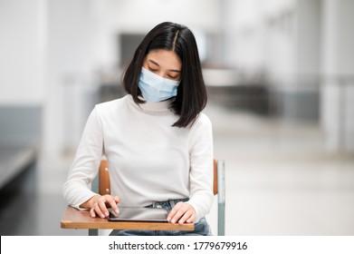 Eine Studentin, die eine Maske trägt und im Klassenzimmer liest