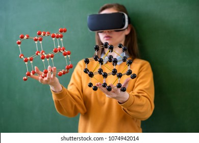 Female student wearing virtual reality glasses, holding molecular structure model. Science class concept. Education, VR, New Technologies and Teaching Methods concept.