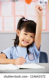 Female Student Working At Desk In Chinese School Classroom
