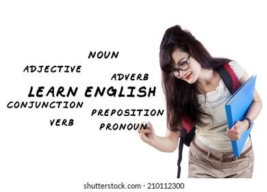 Female student writes english language materials on whiteboard