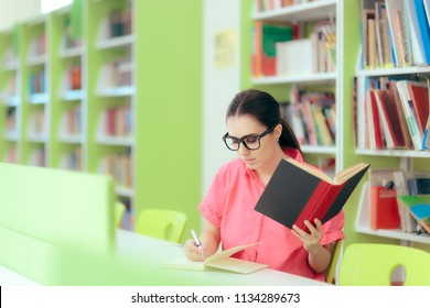 Female Student Writing an Essay Assignment in School Library. Studious university girl quoting from textbooks in essay