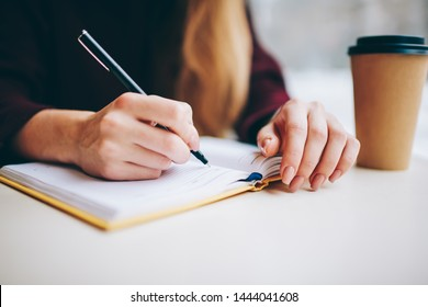Female student writing organisation plan in textbook for education using pen for making notes, cropped image of woman's hand processing information for university course work in knowledge notepad