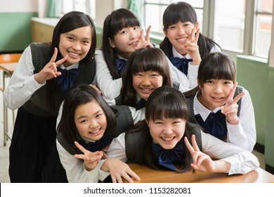 Female students of Japanese to peace sign