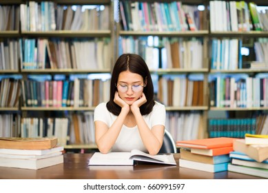 Female students wearing reading glasses in library with black background. book shelf