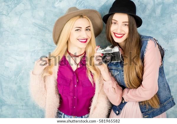 Female stylish friends having fun with photo camera on the blue wall background