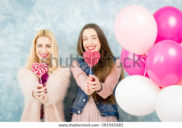 Female stylish friends having fun with candy and baloons on the blue wall background