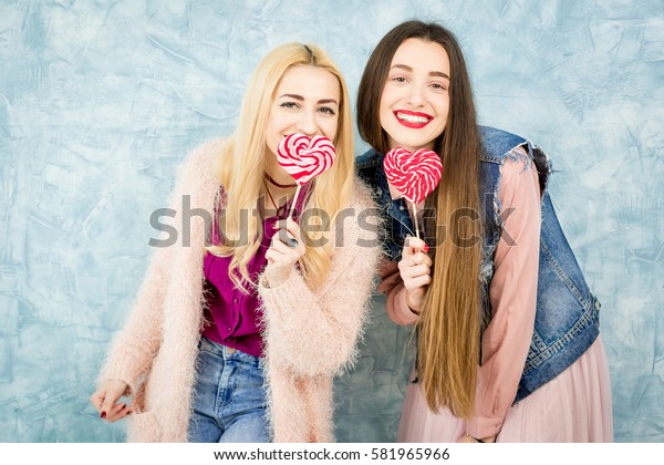 Female stylish friends having fun with candy on the blue wall background