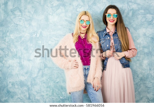 Female stylish friends having fun together on the blue wall background