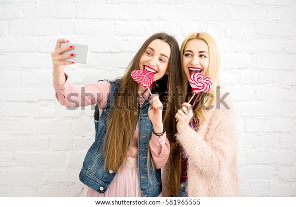 Female stylish friends making selfie photo with red candies on the white wall background