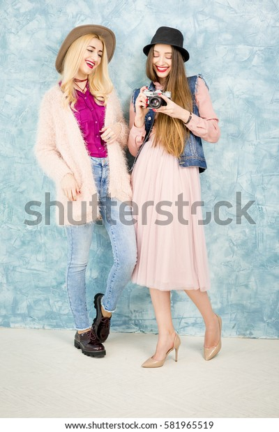 Female stylish friends standing with photo camera on the blue wall background