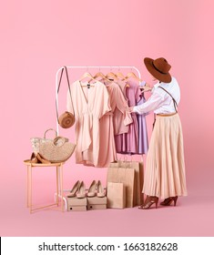 Female stylist near rack with modern clothes on color background