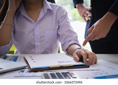 Female subordinate receiving reprimand from boss for being too late at meeting. Pointing on wristwatch. Time management and punctuality at work concept.