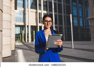 Female successful business worker online banking via touch pad computer while standing outside company during break at job