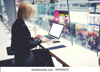 Female successful businesswoman is using for distance work laptop computer with empty copy screen for your advertising text message. Hipster girl is searching information on web page via net-book