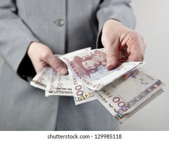 Female in suit handing over some swedish 500 notes