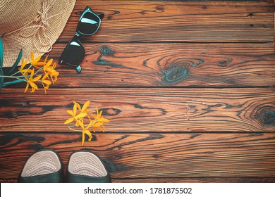 Female sun hat, sandals, sunglasses and orchids on brown wooden surface