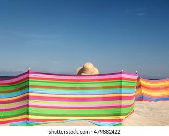 Female sunbather in straw hat relaxing on the beach behind windbreak