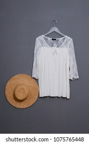female sundress clothes hanging with straw hat on gray background