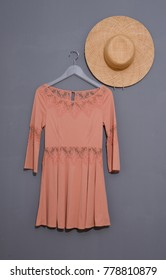 female sundress clothes with hat on hanging - gray background