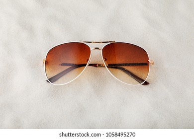 Female sunglasses with no name on the sand, top view