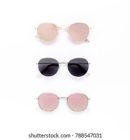 Female sunglasses on white background. Flat lay, top view.