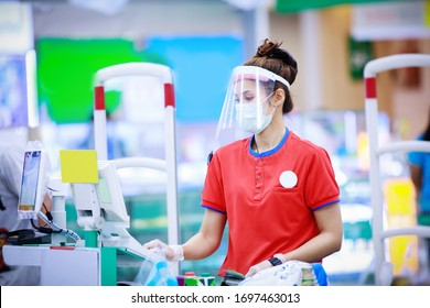 female supermarket cashier in medical protective mask and face shield working at supermarket. covid-19 spreading outbreak