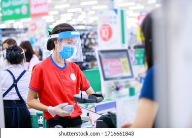 female supermarket cashier in medical protective mask and face shield working in grocery store. covid-19 spreading outbreak